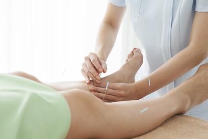 Women acupuncturist providing acupuncture for incontinent patient